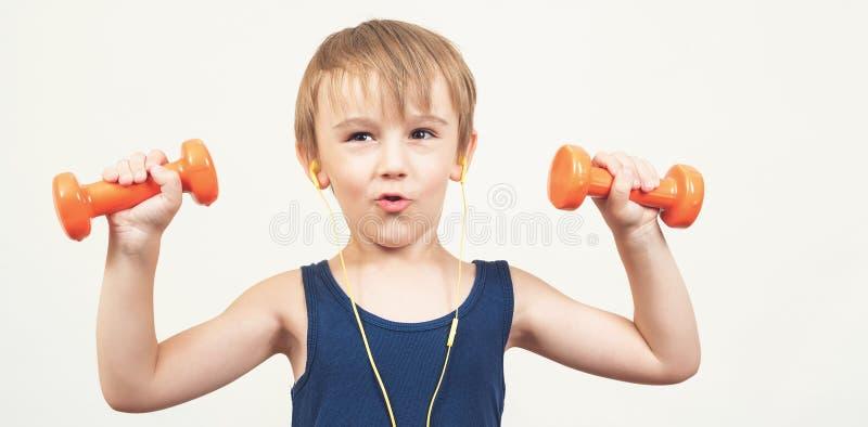 与哑铃的健康强的孩子在白色背景 微笑的男孩做着体育锻炼 r ?? 库存照片
