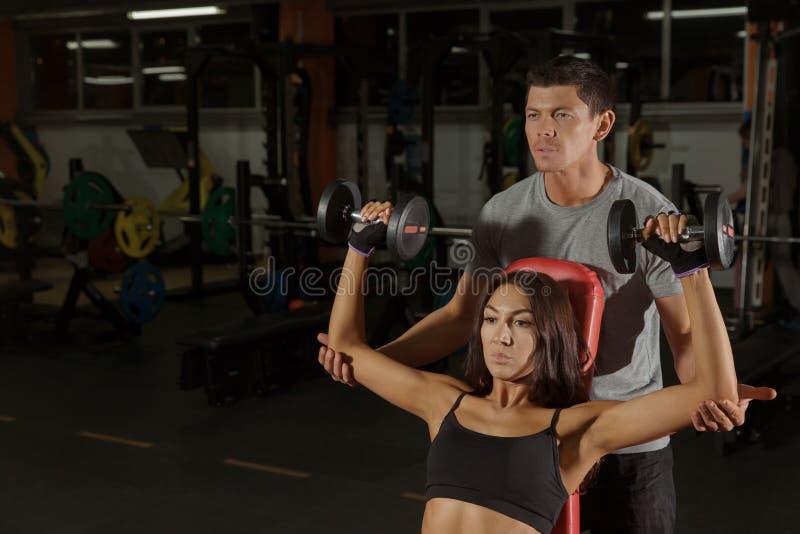 与哑铃的夫妇训练在体育健身房 免版税库存图片