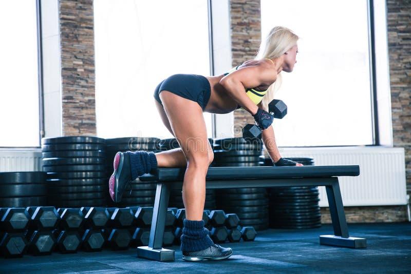 与哑铃的妇女锻炼在长凳 库存图片