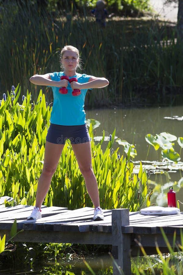 与哑铃的少妇训练在木桥和水 免版税库存照片