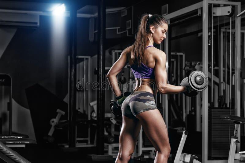 与哑铃的性感的大乳房少妇训练在健身房 免版税库存图片