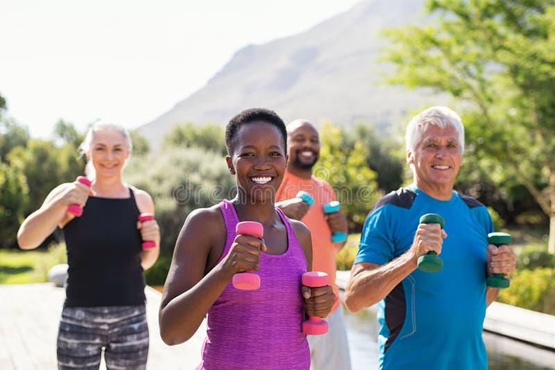 与哑铃的愉快的健身人训练 免版税库存照片