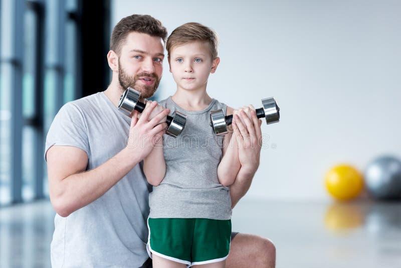 与哑铃的男孩训练与教练一起 图库摄影