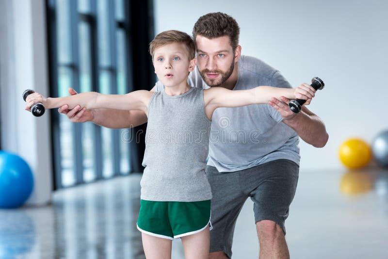 与哑铃的男孩训练与教练一起 库存照片