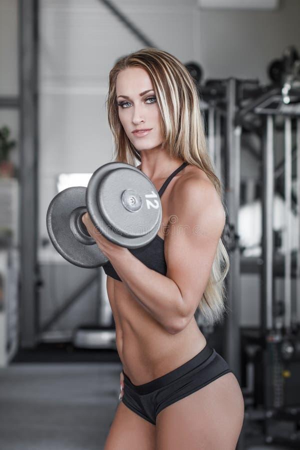 与哑铃的白肤金发的健身模型锻炼 免版税图库摄影