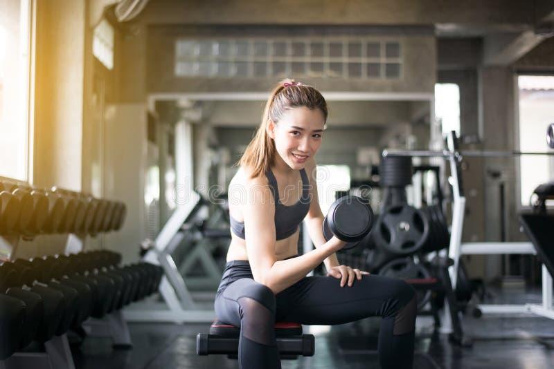 与哑铃的运动的亚洲美女锻炼,女性在运动服做锻炼在健身房 免版税库存图片