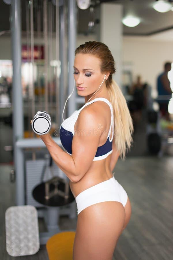 与哑铃的年轻白肤金发的强的妇女锻炼在健身房 库存图片