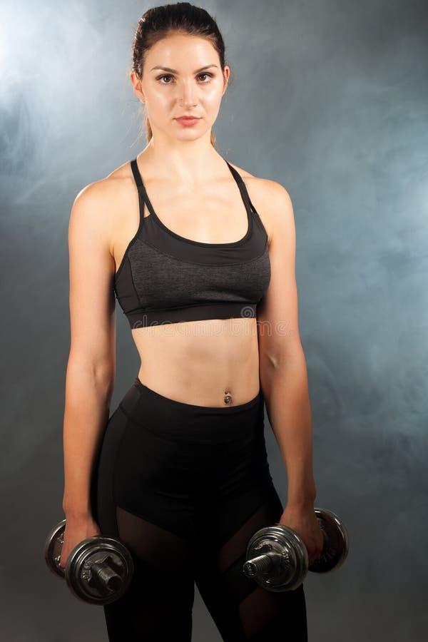 与哑铃a的活跃年轻运动的西班牙妇女锻炼 免版税库存照片