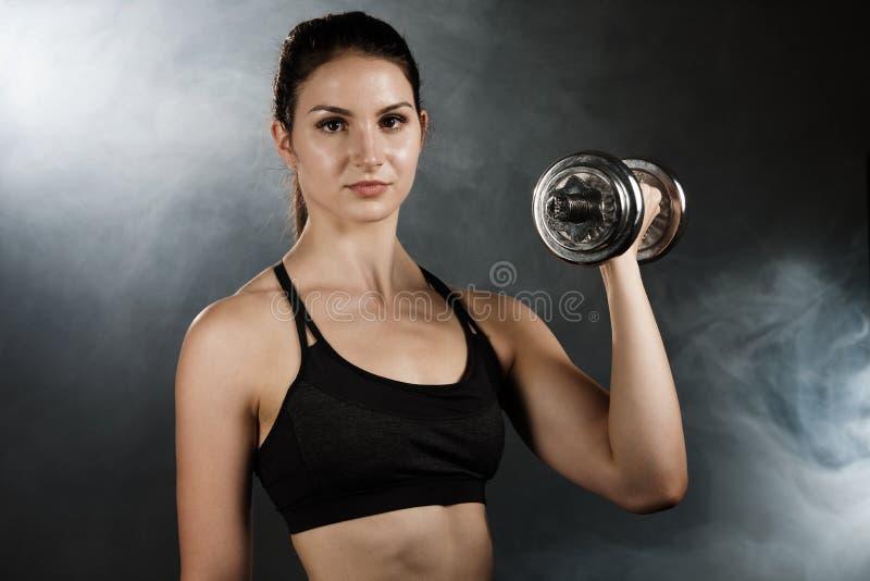 与哑铃isolat的活跃年轻运动的西班牙妇女锻炼 库存照片