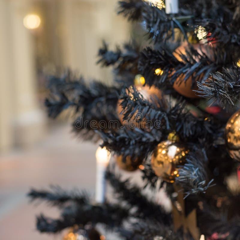 与哥特式黑暗的装饰,金黄球,在黑暗的蜡烛的被弄脏的抽象圣诞树在内部 xmas 关闭 免版税库存图片