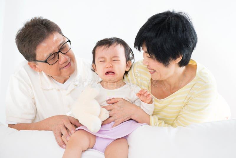 与哭泣的婴孩的亚洲家庭 免版税库存照片