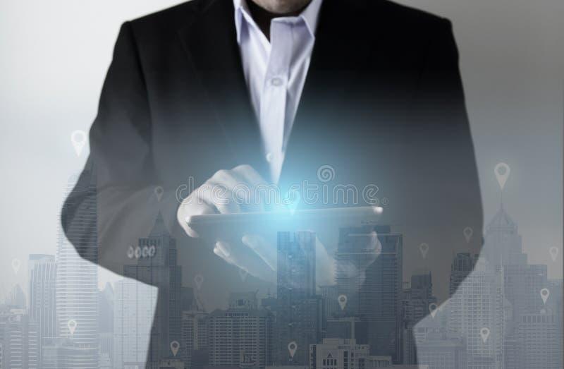与商人的技术使用新的片剂连接用城市地平线快速的技术 免版税库存照片