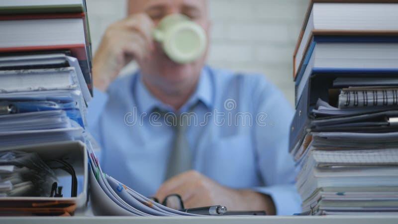 与商人的模糊的照片在认为的档案饮用的咖啡 库存照片