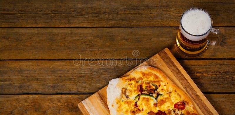 与啤酒杯的新鲜的薄饼在木桌上服务 免版税库存照片