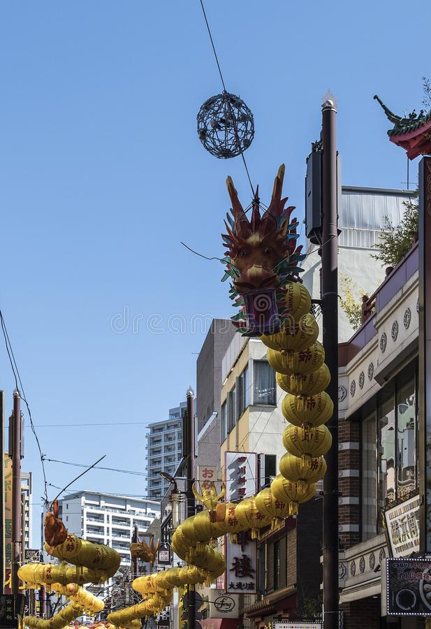 与嘴的中国龙开放在显示在有黄色灯笼的横滨,日本唐人街 库存照片
