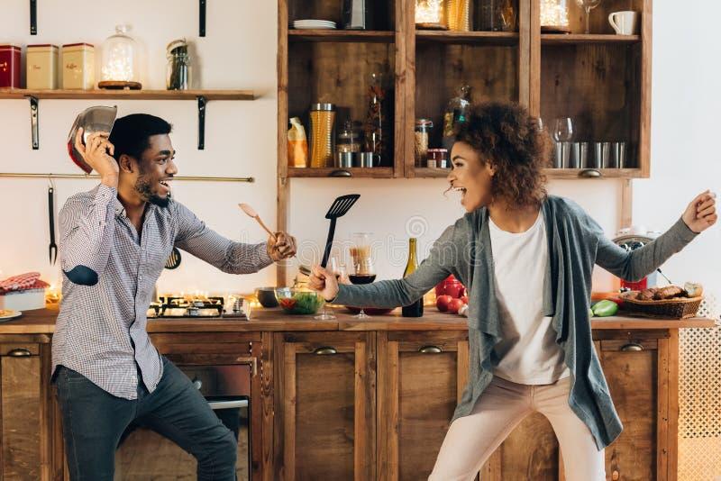 与器物工具的滑稽的夫妇战斗在厨房里 库存照片
