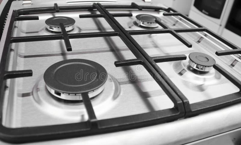 与四台燃烧器厨房的,不锈钢表面的新的现代煤气炉 库存照片