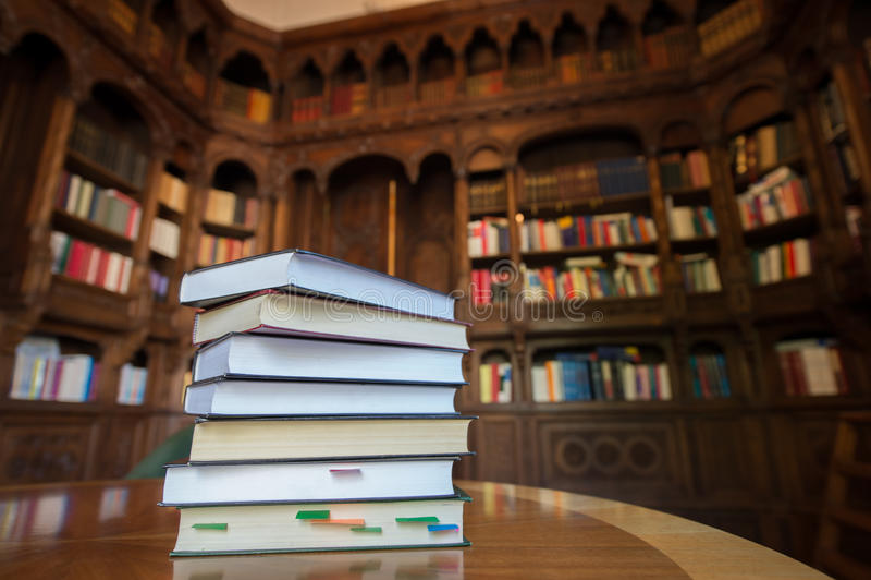 与图书馆的被堆积的书在背景中 免版税库存图片