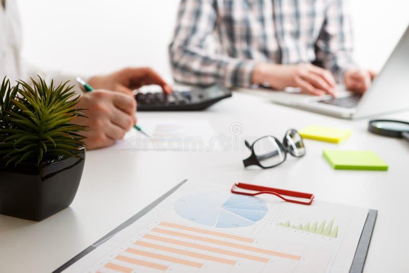 与图和图表的在背景的文件和笔两位雇员工作 免版税库存图片