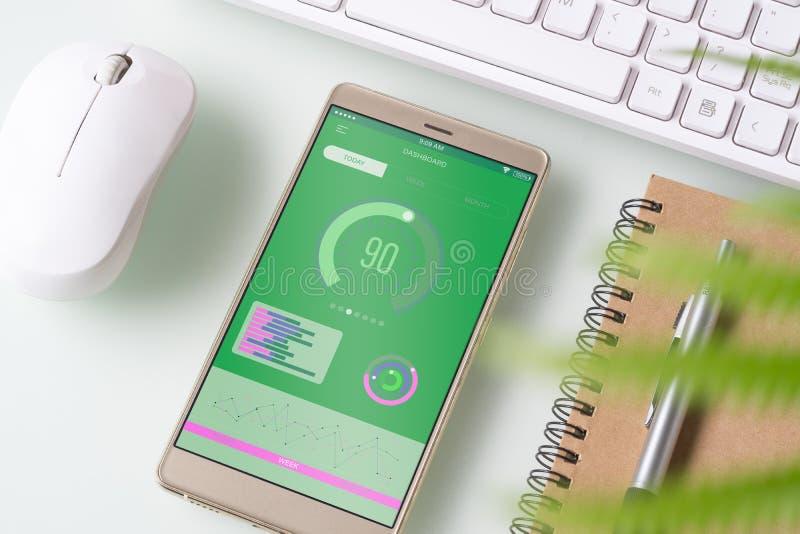 与图表图的办公桌桌顶视图在白色书桌桌上的假装智能手机 业务管理报告通过机动性 免版税库存照片