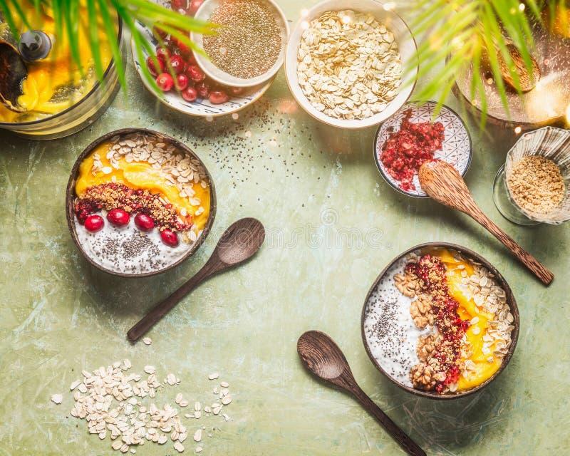与圆滑的人芒果碗的健康干净的夏天早餐桌和热带水果、chia种子酸奶布丁和蔓越桔, 图库摄影