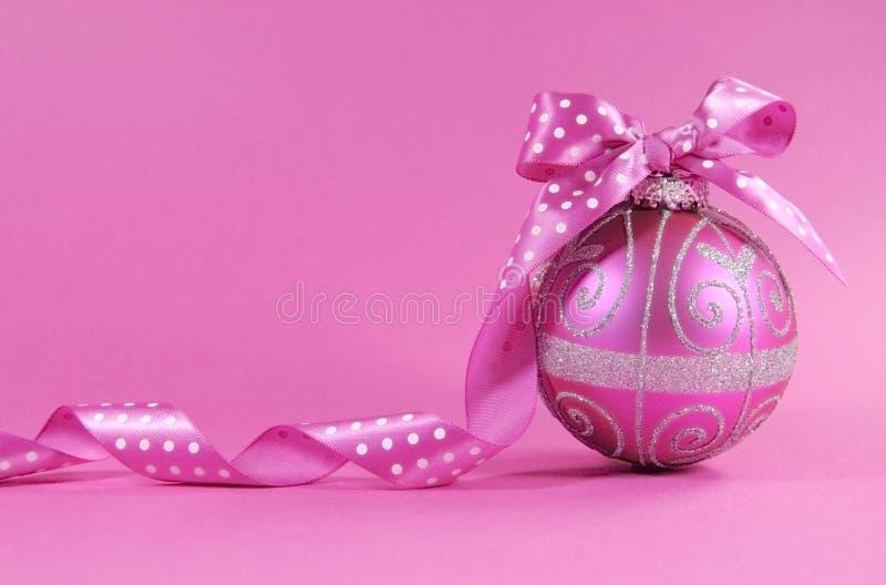 与圆点丝带的美丽的紫红色的桃红色欢乐中看不中用的物品装饰品在与拷贝空间的女性桃红色背景 免版税图库摄影