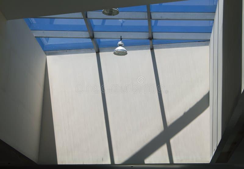 与圆的灯和屋顶窗口的现代大厦照明设备 有太阳光和阴影的混凝土墙 库存照片