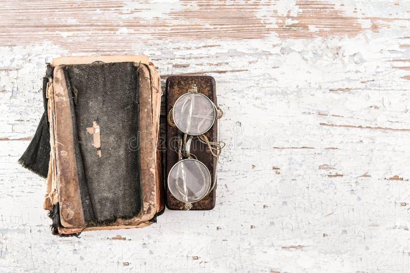 与圆的眼镜20世纪20年代的古老在木桌、顶视图、空间文本的或设计元素上的祈祷书和案件 免版税库存图片