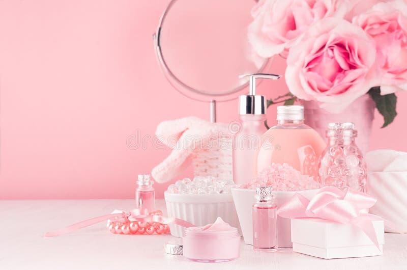 与圆的镜子、花和化妆用品产品的柔和的少女梳妆台-玫瑰油,腌制槽用食盐,奶油,香水 库存图片