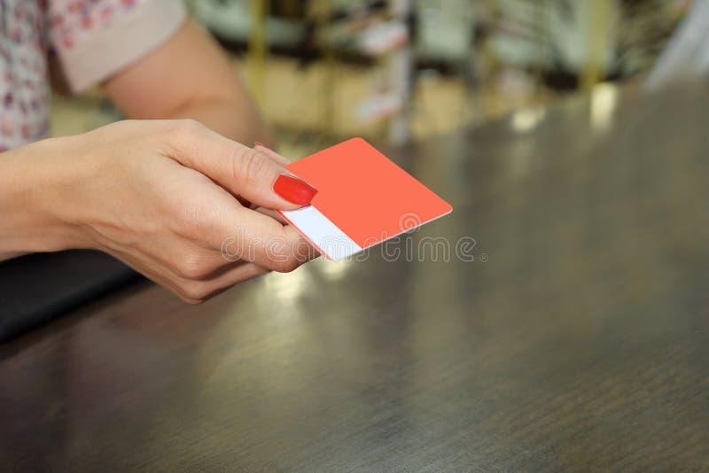 与圆角落的手举行空白红色忠诚卡片大模型 握胳膊的模板的简单的vip嘲笑 免版税库存图片