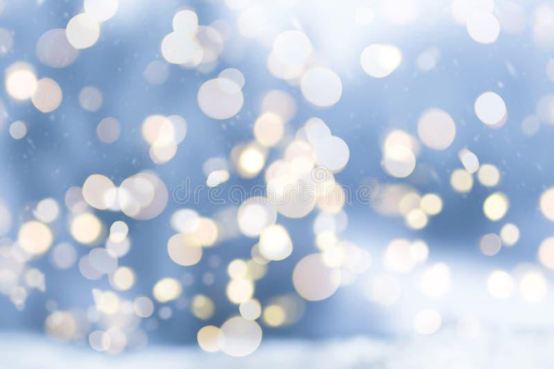 与圆bokeh光的模糊的多雪的冬天圣诞节背景 免版税图库摄影