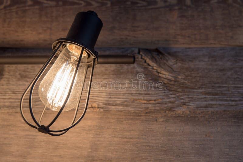 与土气金属电灯泡笼子的卫生间照明设备在被风化的木头背景  免版税库存照片