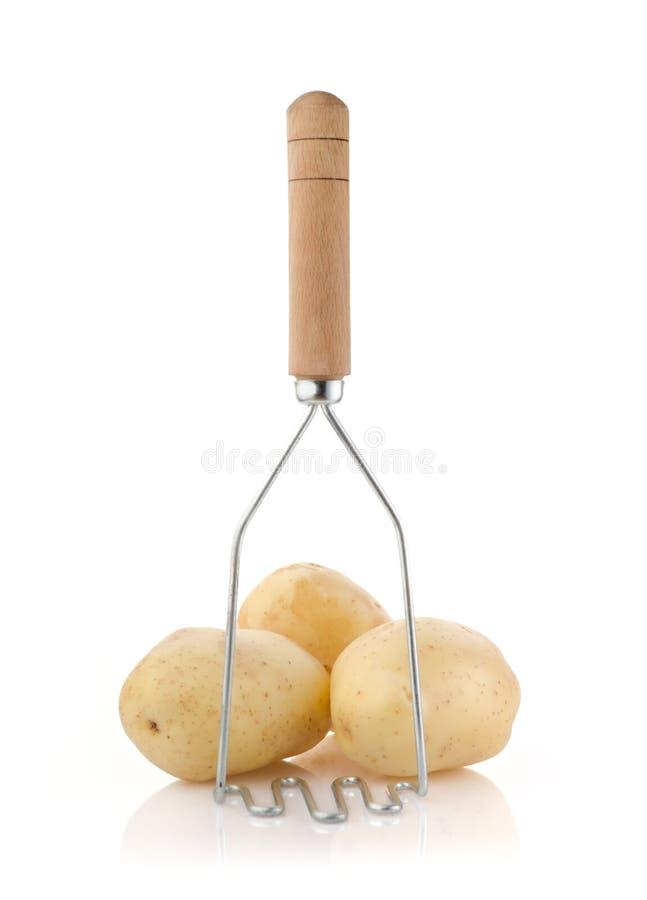 与土豆捣碎器的土豆在白色 免版税库存照片