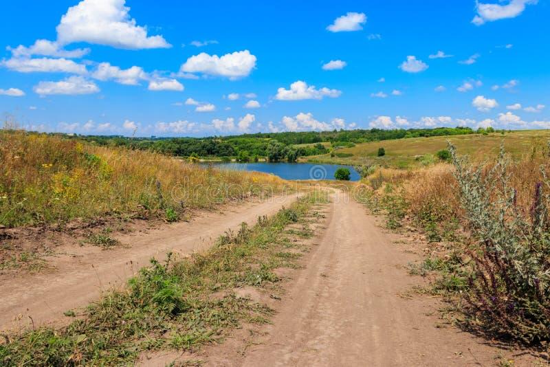 与土路向湖和天空蔚蓝的夏天风景与白色云彩 免版税库存照片