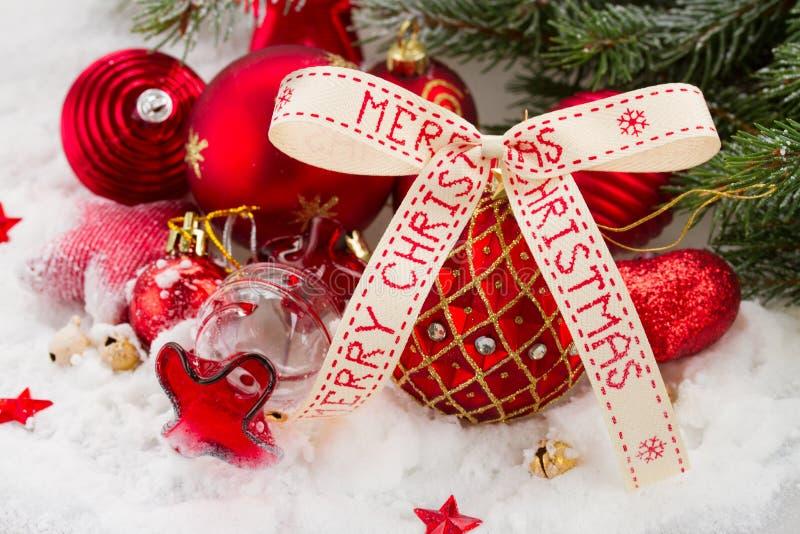 与圣诞快乐丝带的红色球 免版税库存图片