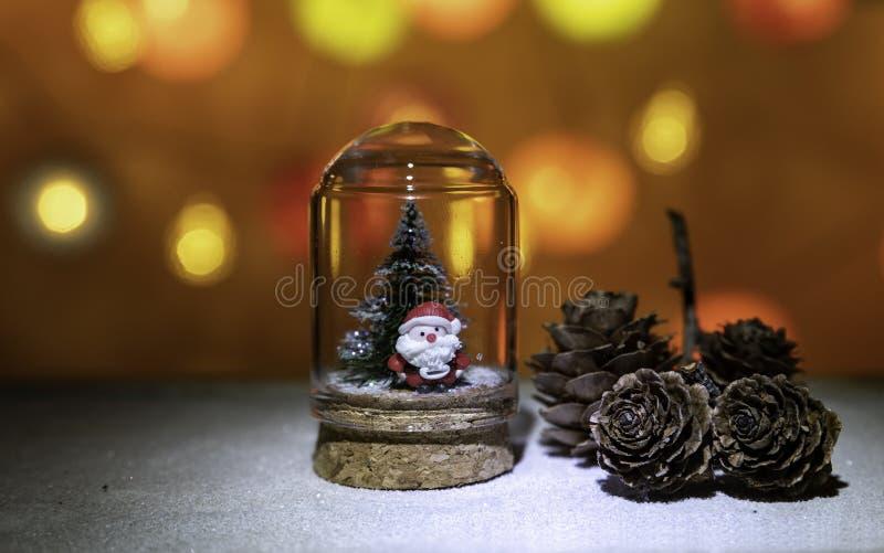 与圣诞树的圣诞老人项目在杉木锥体附近的玻璃管从圣诞灯背景 库存照片