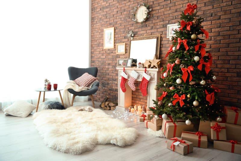 与圣诞树的室内部和礼物临近装饰壁炉 免版税库存图片
