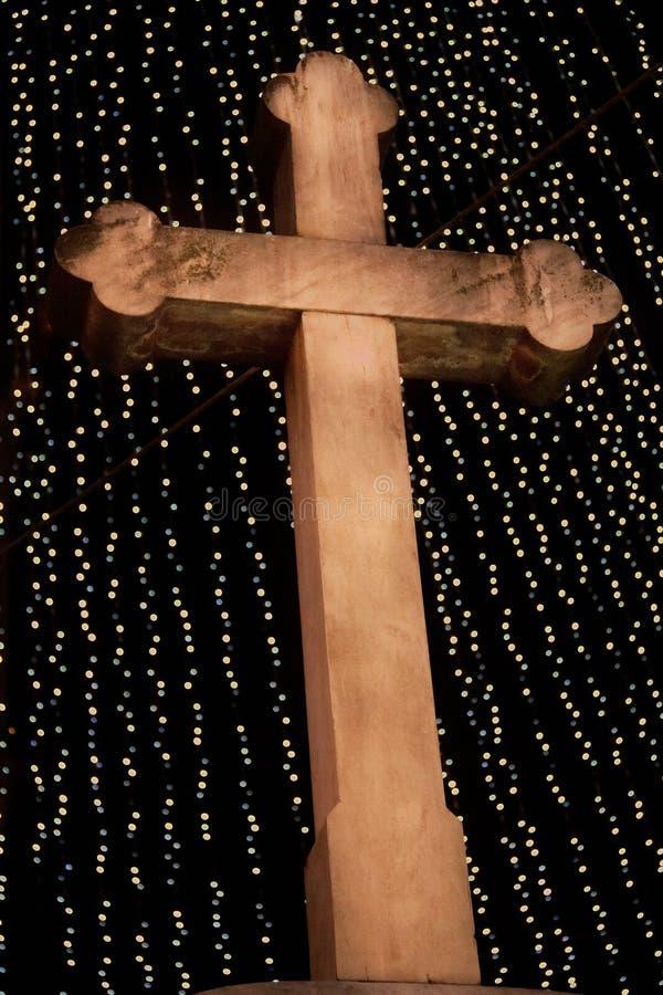 与圣诞灯和夜空的木基督徒十字架 免版税库存照片