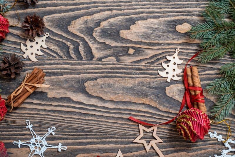 与圣诞礼物,杉木锥体,在木背景的红色装饰的圣诞节背景与冷杉分支 Xmas和愉快新 库存照片