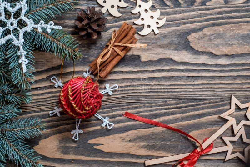 与圣诞礼物,杉木锥体,在木背景的红色装饰的圣诞节背景与冷杉分支 Xmas和愉快新 免版税库存照片