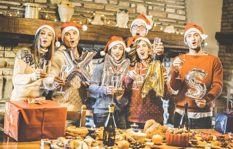 与圣诞老人帽子的朋友小组庆祝圣诞节打过工用香槟和甜点食物的在晚餐会-寒假概念 免版税图库摄影