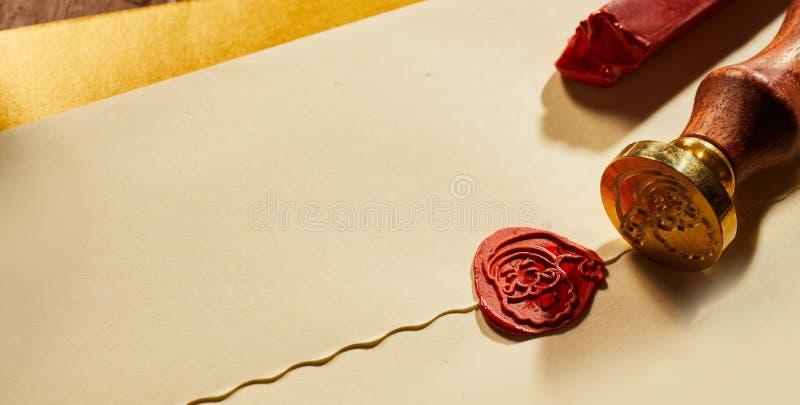 与圣诞老人项目封印的被密封的圣诞节信封在红色蜡的在关闭的葡萄酒豪华纸与拷贝空间的看法 库存照片