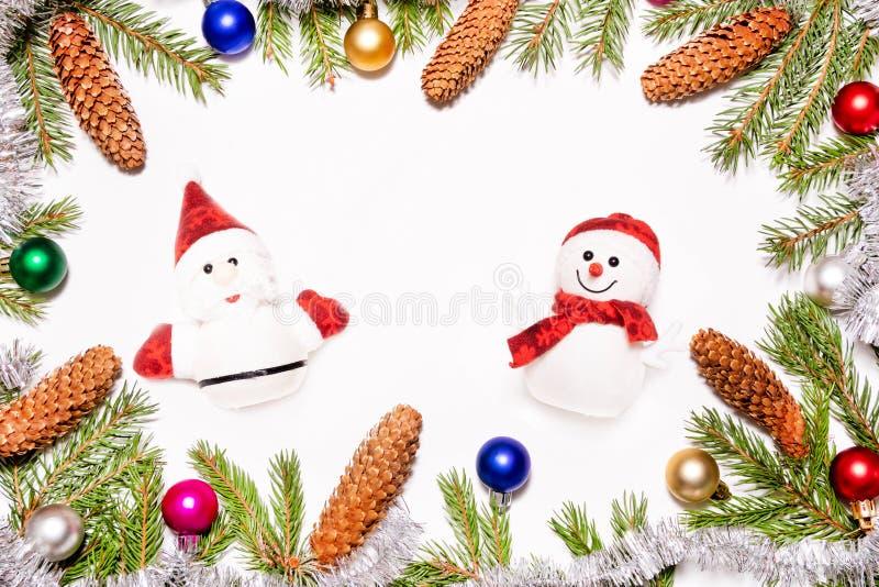 与圣诞老人项目的圣诞装饰和与杉树分支五颜六色的玩具和锥体的雪人框架在白色背景 免版税库存照片