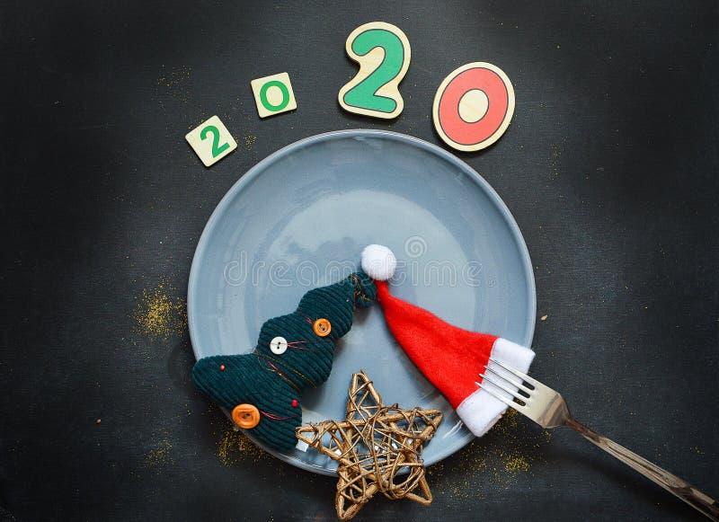 与圣诞节帽子的新年2020样式舱内甲板位置顶视图,圣诞树,在黑暗的背景的星 ??  免版税库存图片