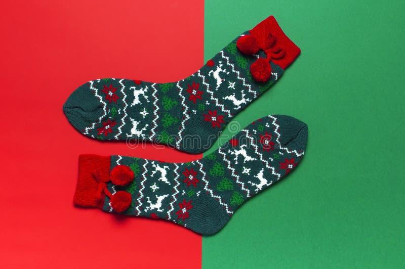与圣诞节新年装饰品的羊毛袜子在红色背景顶视图平的位置 假日概念,欢乐袜子,提出Xmas 免版税图库摄影