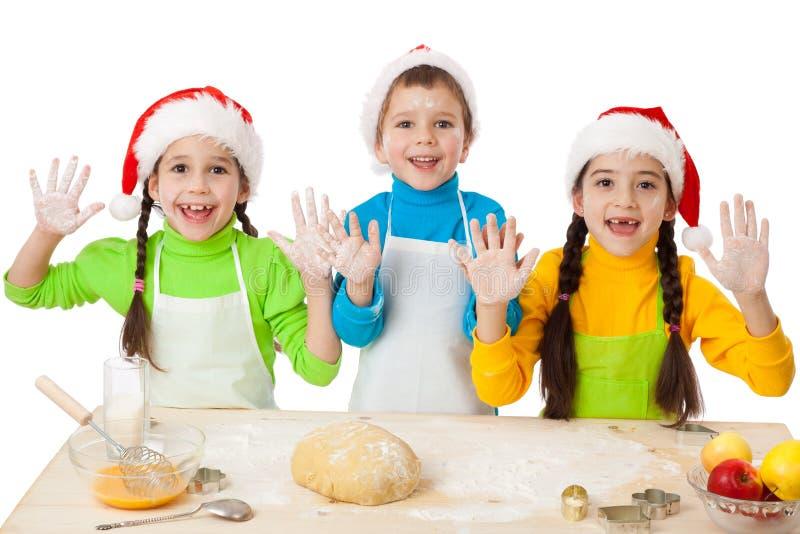 与圣诞节烹调的三个孩子 免版税库存图片