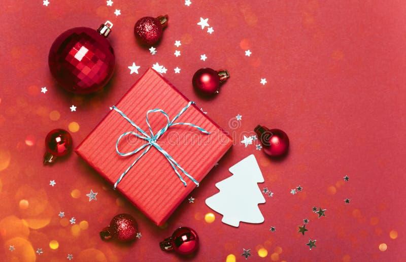 与圣诞节球的圣诞节红色背景和提出用落在他们的糖果和雪 库存照片