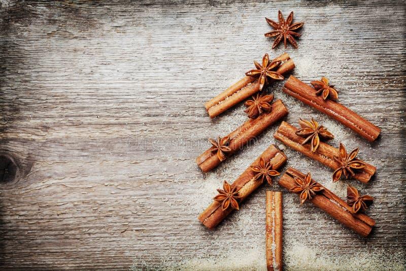 与圣诞节由香料肉桂条、茴香星和蔗糖做的杉树的圣诞卡在土气木背景 免版税库存图片