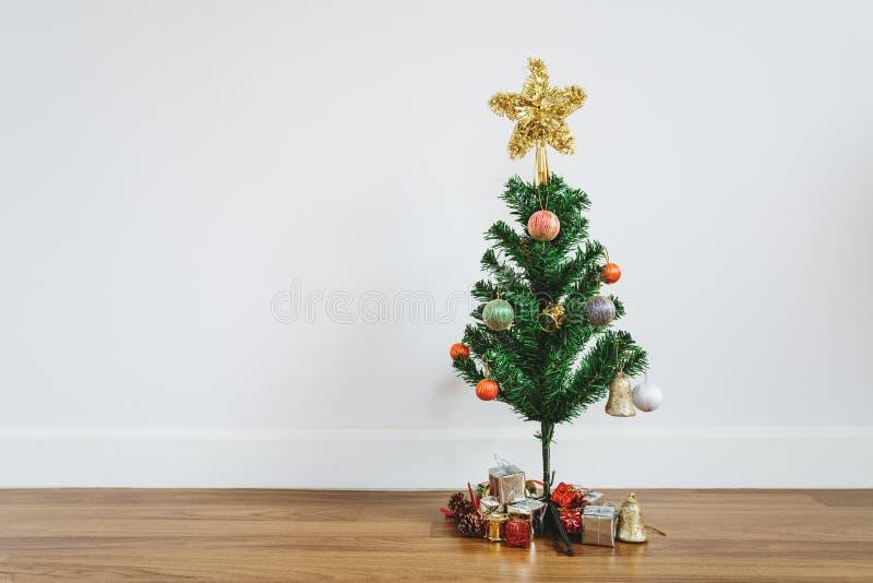 与圣诞节礼物和装饰的圣诞树在木地板上,在客厅 免版税库存图片