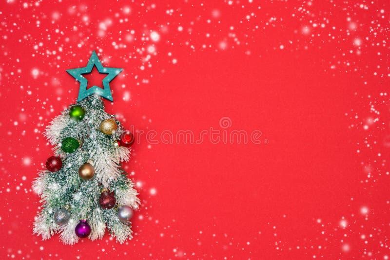 与圣诞节装饰品的装饰圣诞树在红色backgr 库存照片
